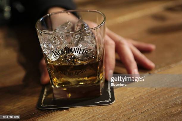 A bartender places a glass of Jack Daniel's whiskey on a coaster for an arranged photograph during a media preview of the Jack Daniel's Lynchburg...