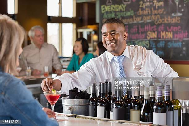 Bartender placing garnish in cocktail for customer at happy hour