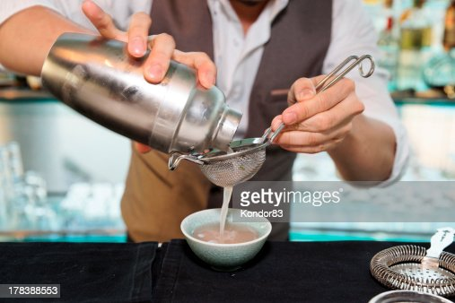 Bartender pouring a cocktail through a sieve : Stock Photo
