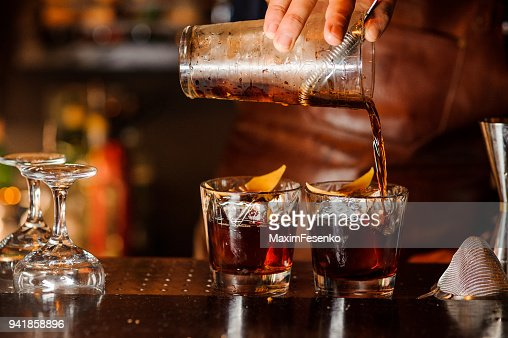 Bartender pouring alcoholic drink into the glasses : Stock Photo