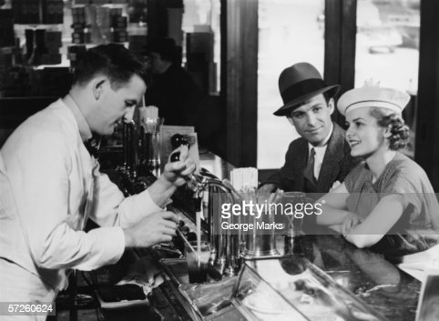 Bartender pouring beer for young couple in bar, (B&W) : Stock Photo
