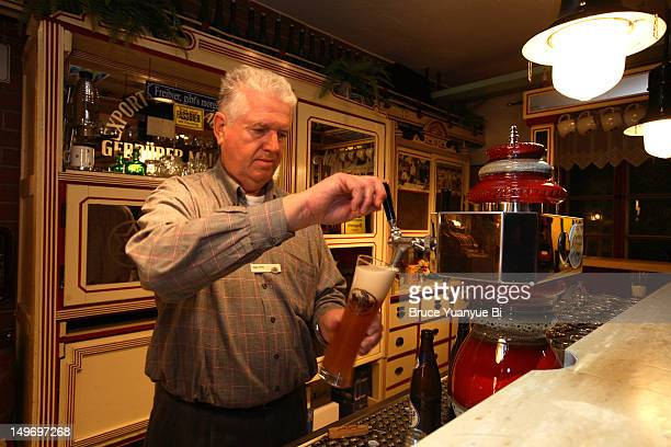 Bartender pouring beer in bar of Maisel's Brewery and Cooperage Museum.