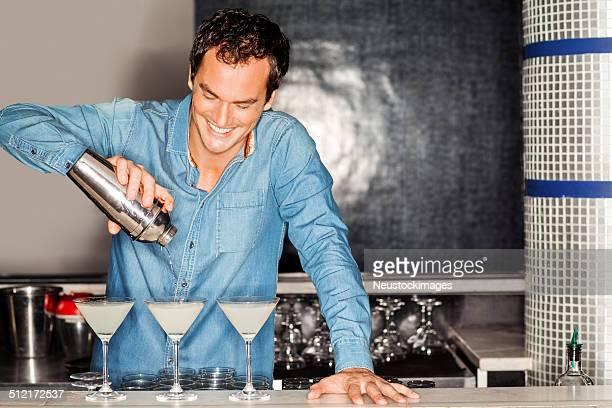 Barkeeper gießen Cocktail im Martini-Gläser in-Schalter