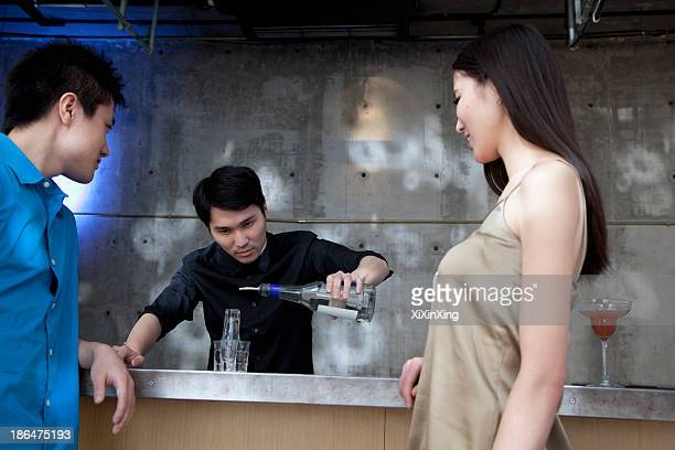 Bartender pouring licour on shot glass pyramid