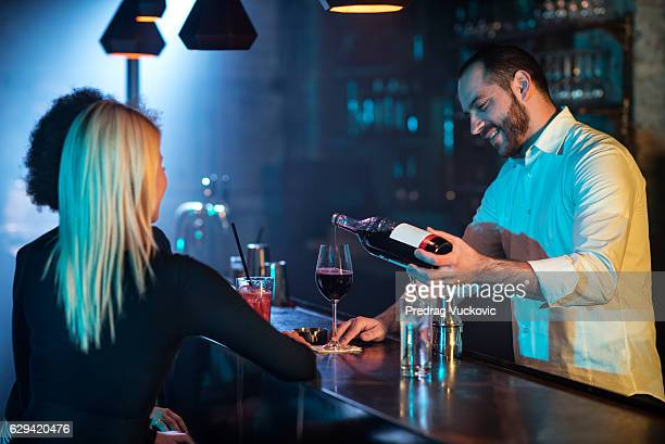 Bartender pouring red wine to customers
