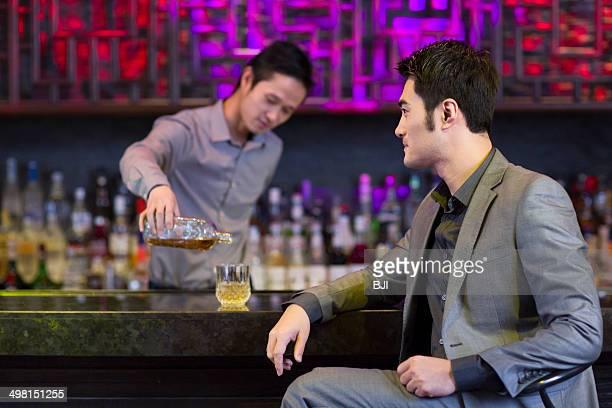 Bartender pouring wine for customer
