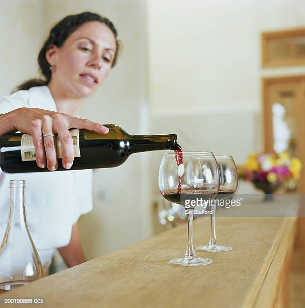 Bartender pouring wine into glass