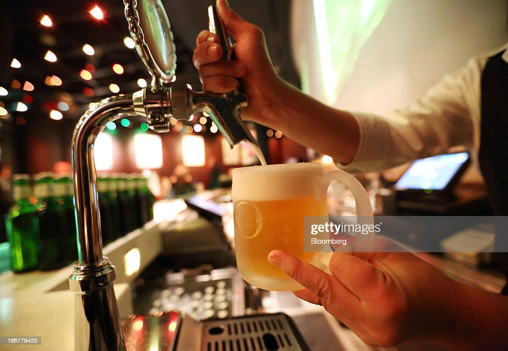 A bartender pours a glass of Heartland brand beer, brewed by Kirin Holdings Co., in the Heartland bar at the Roppongi Hills complex, operated by Mori Building Co., at night in Tokyo, Japan, on Tuesday, April 17, 2013. While financial firms have cut staff in Japan, technology companies have boosted hiring, and as bankers vacated offices at Roppongi Hills, companies including Google Inc. and Lenovo Group Ltd. moved in. As early as this month, Apple Inc. will also make the complex its home in Japan, two people familiar with the plan said in January. Photographer: Tomohiro Ohsumi/Bloomberg via Getty Images