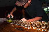 A bartender pours a line of shots