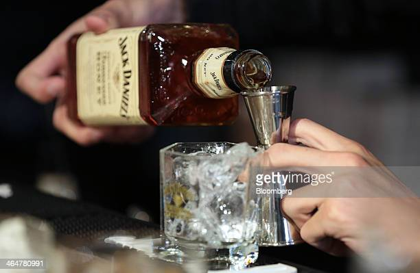 A bartender pours Jack Daniel's Tennessee Honey liqueur into a jigger during a media preview of the Jack Daniel's Lynchburg Barrel House an official...