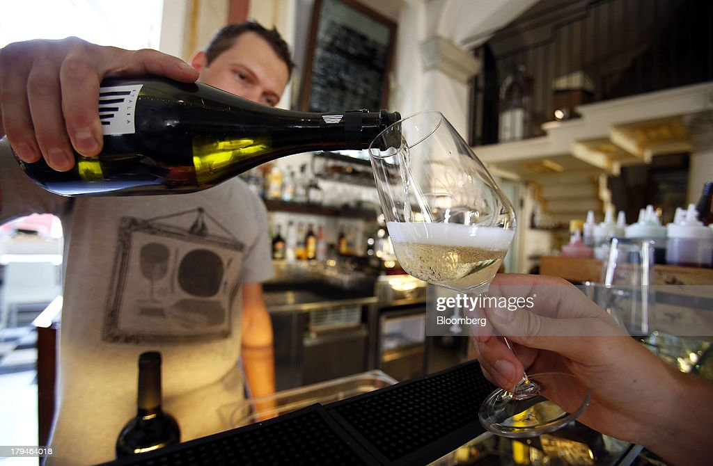 A bartender pours Prosecco wine into a glass for an Italian oenologist to test for authenticity at a restaurant in Treviso, Italy, on Tuesday, Sept. 3, 2013. Italy's Agriculture Ministry has begun to investigate suspected sales of imitation Prosecco sparkling wine in its native Veneto region. Photographer: Alessia Pierdomenico/Bloomberg via Getty Images
