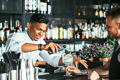 Mixed race male expert bartender is serving some tonic for a cocktail at the bar counter while a smiling waiter is holding the cocktail glass