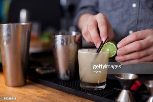 Bartender preparing a cocktail with lime garnish