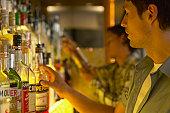 'Bartender reaching for bottle of spirits, close-up'
