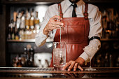Bartender in the white shirt and brown leather apron stirring an ice cubes in the cocktail on the bar counter