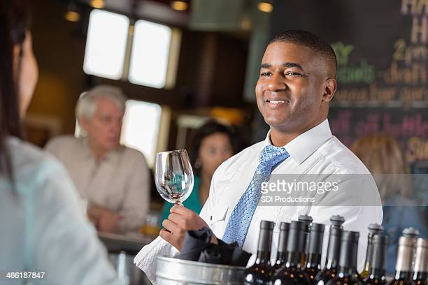 Bartender talking with female customer while working in restaurant