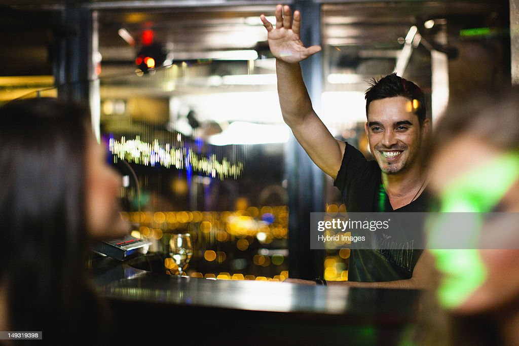Bartender waving to customers in bar : Stock Photo
