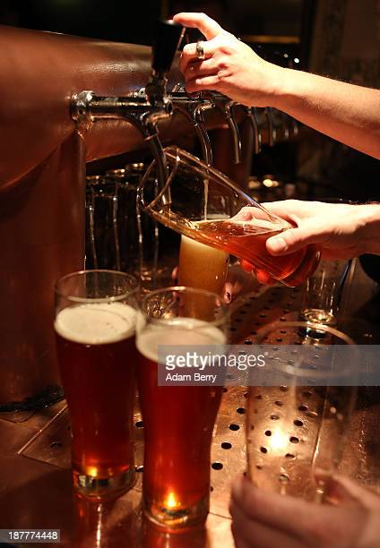 Bartenders at Hops Barley brewpub pour pints of beer on November 12 2013 in Berlin Germany In a country known for centuries for its beer several...
