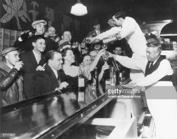 Bartenders at Sloppy Joe's bar pour a round of drinks on the house for a large group of smiling customers as it was announced that the 18th Amendment...