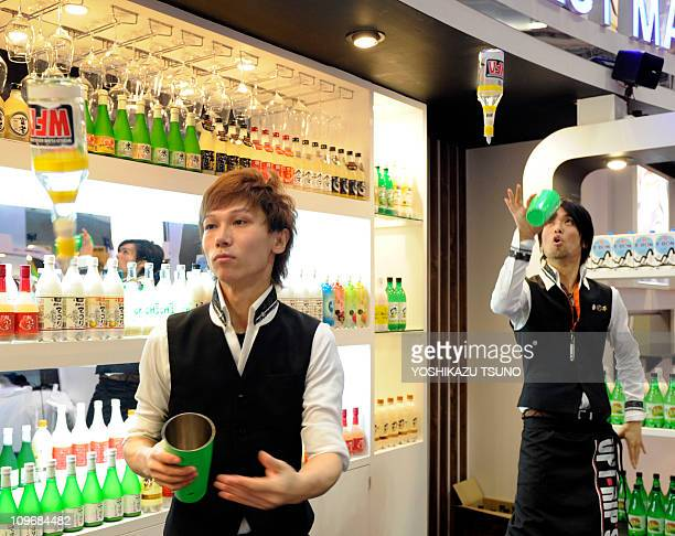 Bartenders juggle bottles of makkolli a Korean liquor for cocktails at the annual 'Foodex' food exhibition in Chiba suburban Tokyo on March 1 2011...
