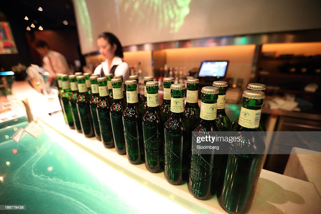 Bartenders work behind bottles of Heartland brand beer, brewed by Kirin Holdings Co., in the Heartland bar at the Roppongi Hills complex, operated by Mori Building Co., at night in Tokyo, Japan, on Tuesday, April 17, 2013. While financial firms have cut staff in Japan, technology companies have boosted hiring, and as bankers vacated offices at Roppongi Hills, companies including Google Inc. and Lenovo Group Ltd. moved in. As early as this month, Apple Inc. will also make the complex its home in Japan, two people familiar with the plan said in January. Photographer: Tomohiro Ohsumi/Bloomberg via Getty Images