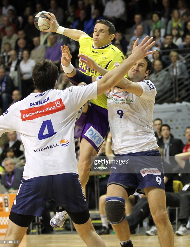 Bartlomiej Jaszka (C) of Berlin is attacked by Domagoj Duvnjak (L) of Hamburg and team mate Igor Vori (R) during the Toyota Handball Bundesliga match between Fuechse Berlin and HSV Hamburg at Max Schmeling hall on March 20, 2011 in Berlin, Germany.