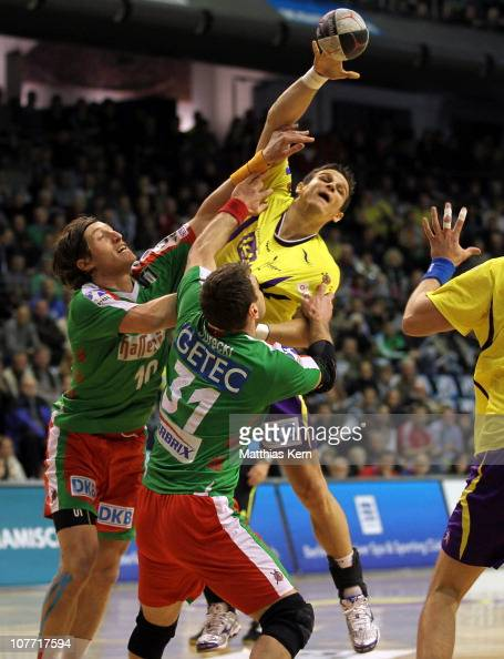 Bartlomiej Jaszka of Berlin is attacked by Fabian van Olphen of Magdeburg and his team mate Bartosz Jurecki during the Toyota Handball Bundesliga...