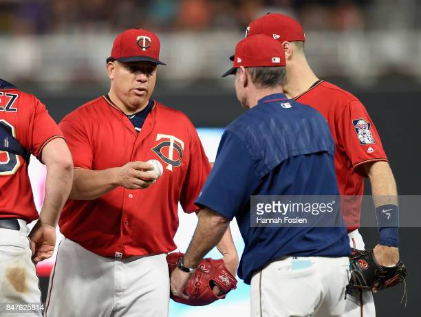 Bartolo Colon of the Minnesota Twins hands the ball to manager Paul Molitor as he leaves the game against the Toronto Blue Jays during the seventh...