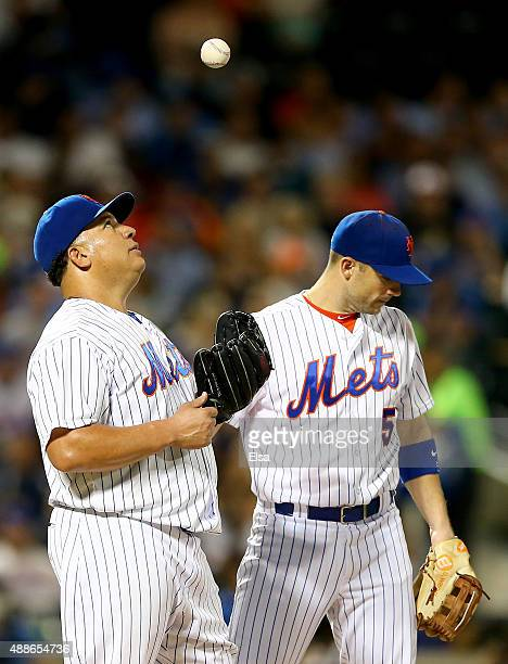 Bartolo Colon of the New York Mets reacts while teammate David Wright stands by as Colon is about to be pulled from the game in the sixth inning...