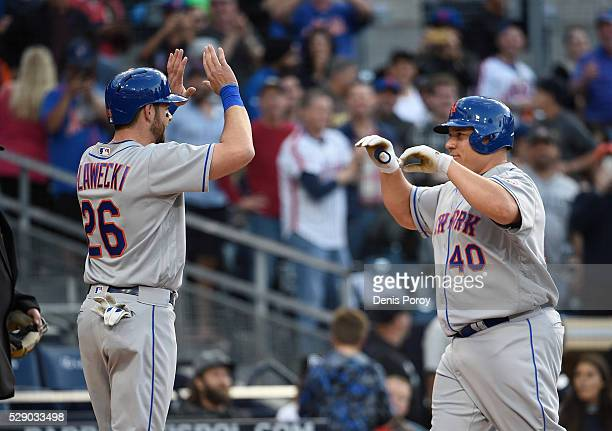 Bartolo Colon of the New York Mets right is congratulated by Kevin Plawecki after hitting a tworun home run for the first of his career during the...