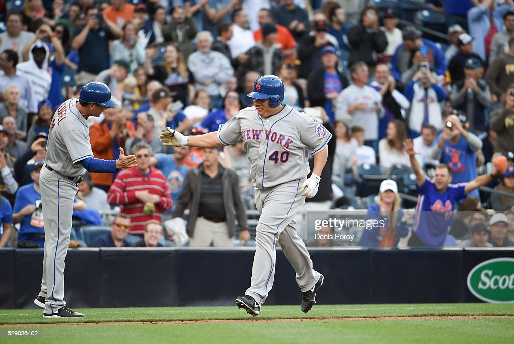 Bartolo Colon #40 of the New York Mets, right, is congratulated by Tim Teufel #11 after hitting a two-home run home run for the first of his career during the second inning of a baseball game against the San Diego Padres at PETCO Park on May 7, 2016 in San Diego, California.