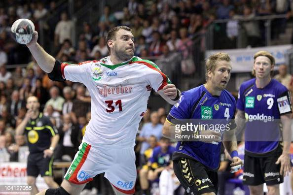 Bartosz Jurecki of Magdeburg scores against Oliver Roggisch and Borge Lund of Rhein Neckar Loewen during the Toyota Handball Bundesliga match between...