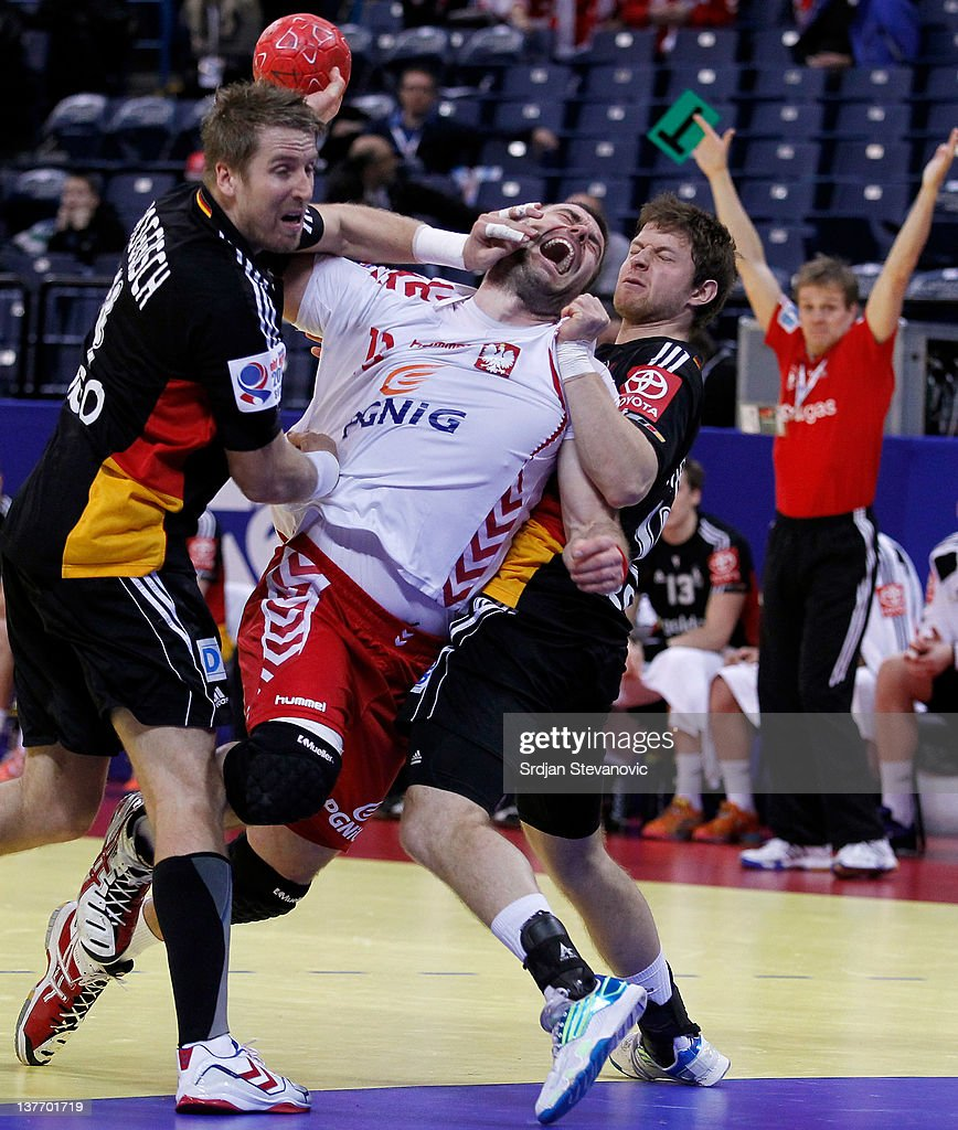 Bartosz Jurecki (C) of Poland battles with Oliver Roggisch (L) and Martin Strobel (R) of Germany during the Men's European Handball Championship 2012 second round group one match between Poland and Germany at Arena Hall on January 25, 2012 in Belgrade, Serbia.