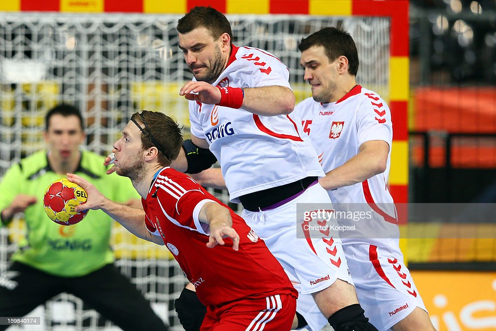 Bartosz Jurecki of Poland (C) defends against Gabor Csaszar of Hungary (L) during the round of sixteen match between Hungary and Poland at Palau Sant Jordi on January 21, 2013 in Barcelona, Spain.