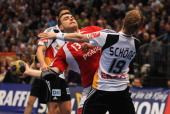 Bartosz Jurecki of Poland is challenged by Christian Schoene of Germany during the international handball friendly match between Germany and Poland...