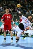 Bartosz Jurecki of Poland scores a goal against Szabolcs Zubai of Hungary during the round of sixteen match between Hungary and Poland at Palau Sant...