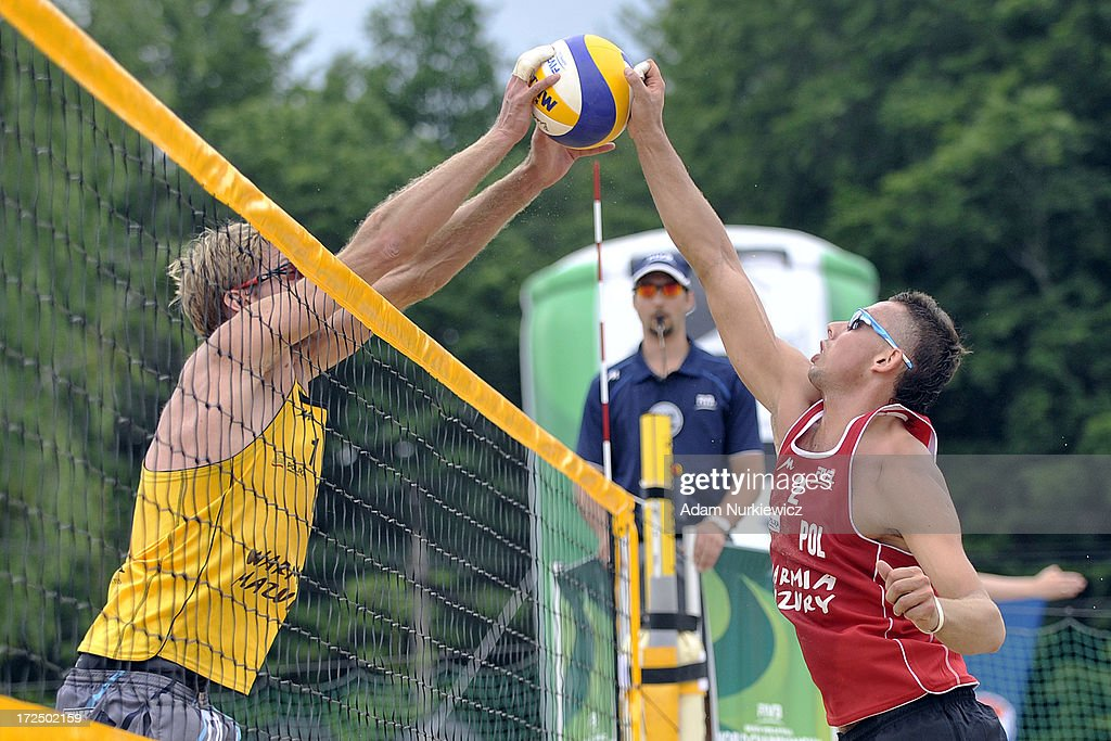 Bartosz Losiak (R) of Poland attacks against Sebastian Dollinger (L) of Germany during Day 2 of the FIVB World Championships on July 2, 2013 in Stare Jablonki, Poland.
