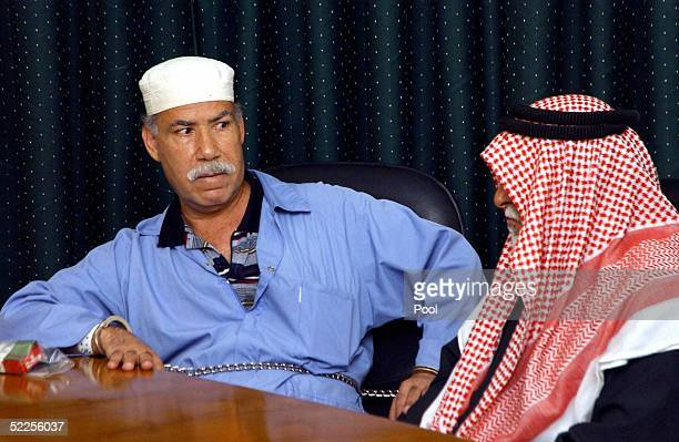Barzan Ibrahim Hassan alTikriti the half brother of former Iraqi dictator Saddam Hussein looks at Awad Hamad alBandar alSadun former chief judge of...