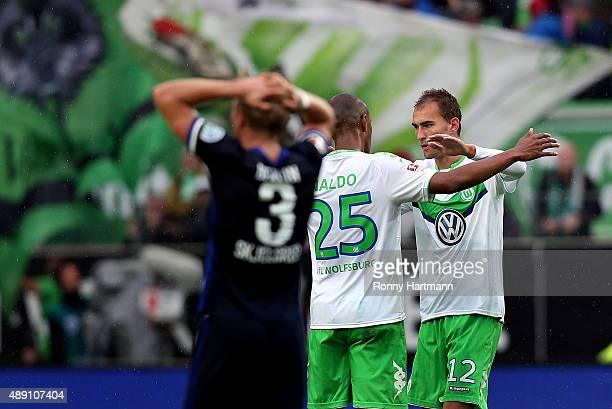 Bas Dost of Wolfsburg celebrates after scoring his team's opening goal with Naldo of Wolfsburg during the Bundesliga match between VfL Wolfsburg and...