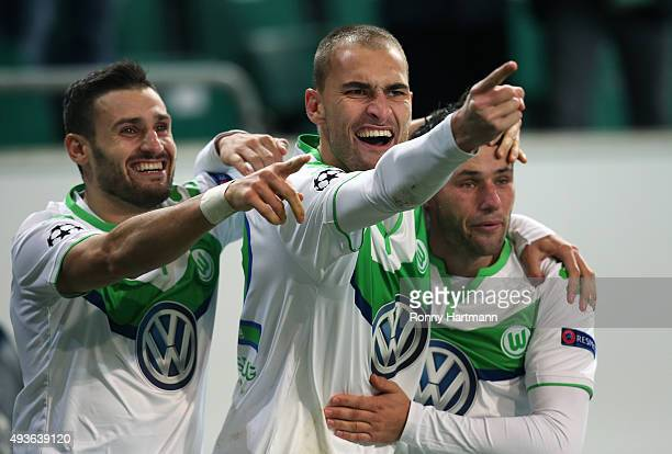 Bas Dost of Wolfsburg celebrates after scoring his team's opening goal with Daniel Caligiuri of Wolfsburg and Christian Traesch of Wolfsburg during...