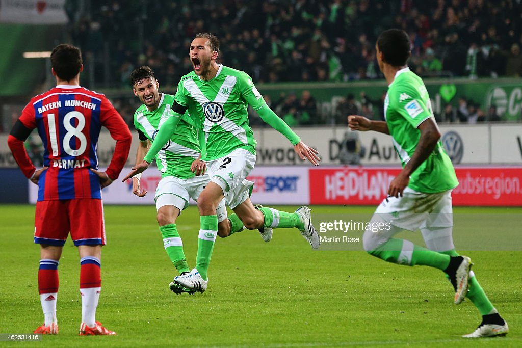 Bas Dost of Wolfsburg celebrates his team's second goal with team mates as Juan Bernat of Muenchen reactsduring the Bundesliga match between VfL Wolfsburg and FC Bayern Muenchen at Volkswagen Arena on January 30, 2015 in Wolfsburg, Germany.