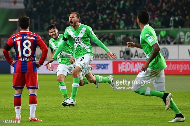 Bas Dost of Wolfsburg celebrates his team's second goal with team mates as Juan Bernat of Muenchen reactsduring the Bundesliga match between VfL...