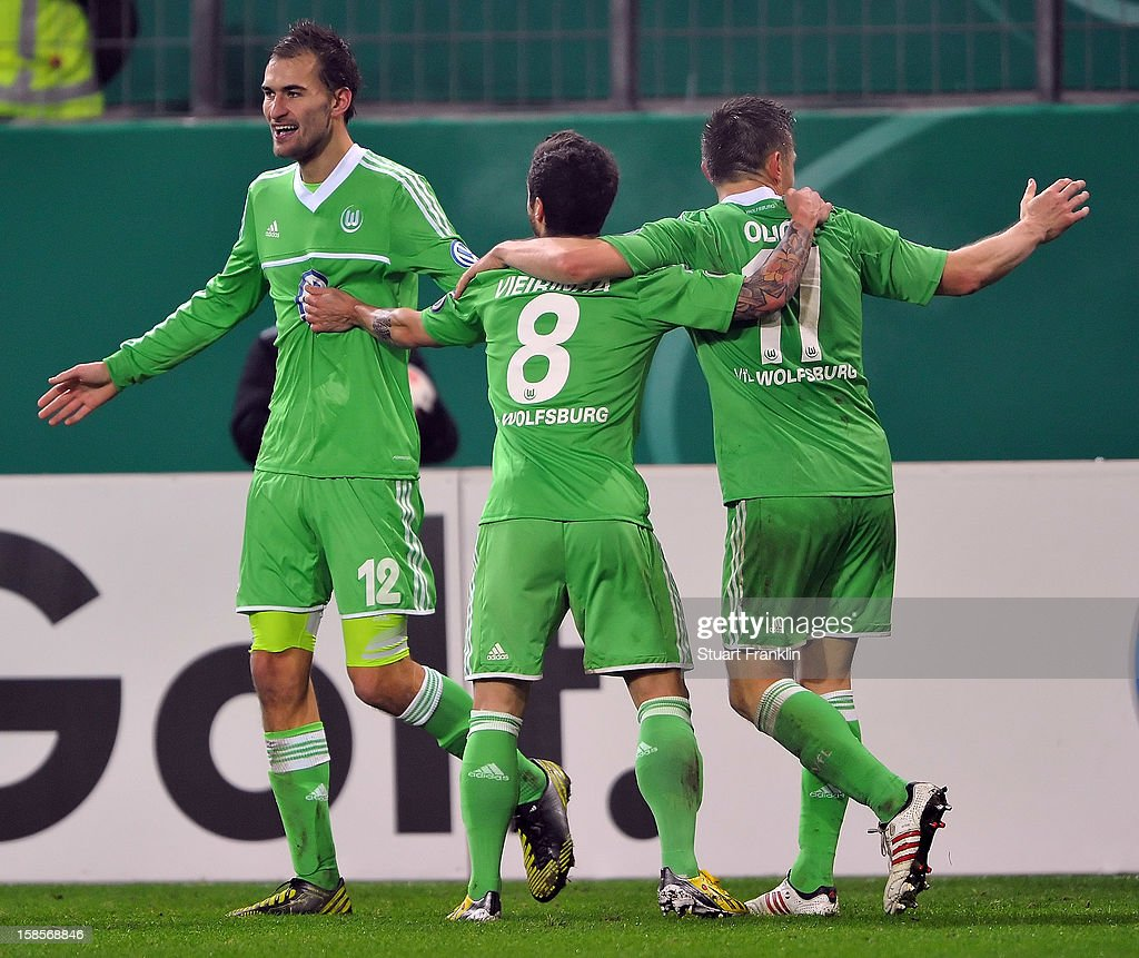 <a gi-track='captionPersonalityLinkClicked' href=/galleries/search?phrase=Bas+Dost&family=editorial&specificpeople=7467816 ng-click='$event.stopPropagation()'>Bas Dost</a> of Wolfsburg celebrates scoring the winning goal with Vierinha and <a gi-track='captionPersonalityLinkClicked' href=/galleries/search?phrase=Ivica+Olic&family=editorial&specificpeople=547277 ng-click='$event.stopPropagation()'>Ivica Olic</a> during the round of 16 of the DFB cup match between VfL Wolfsburg and Bayer Leverkusen at Volkswagen Arena on December 19, 2012 in Wolfsburg, Germany.