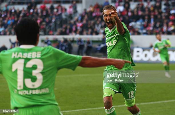 Bas Dost of Wolfsburg celebrates with his team mate Makoto Hasebe after scoring his team's third goal during the Bundesliga match between Fortuna...