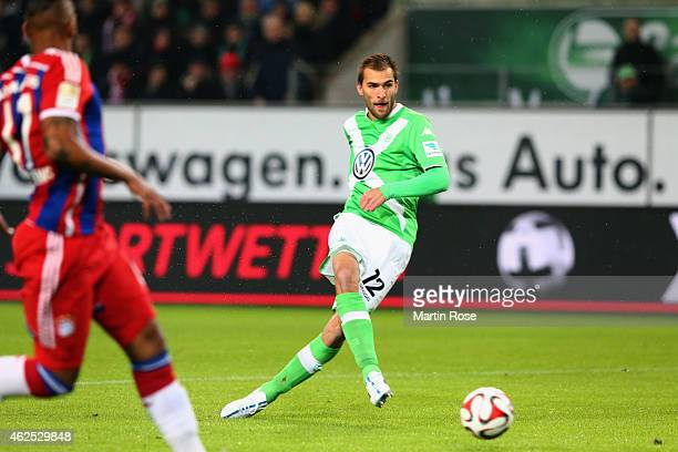 Bas Dost of Wolfsburg scores his team's first goal against Jerome Boateng of Muenchen during the Bundesliga match between VfL Wolfsburg and FC Bayern...