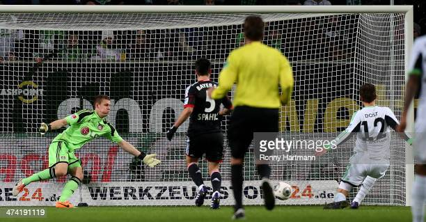 Bas Dost of Wolfsburg scores his team's opening goal against goalkeeper Bernd Leno of Leverkusen during the Bundesliga match between VfL Wolfsburg...