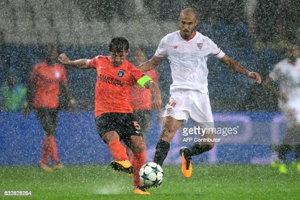 TOPSHOT Basaksehir's Emre Belezoglu vies with Sevilla's Steven N'zonzi during the UEFA Champions League playoff first leg football match between...