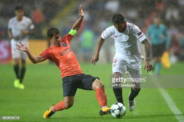 Basaksehir's Emre Belezoglu vies with Sevilla's Walter Montoya during the UEFA Champions League playoff first leg football match between Istanbul...