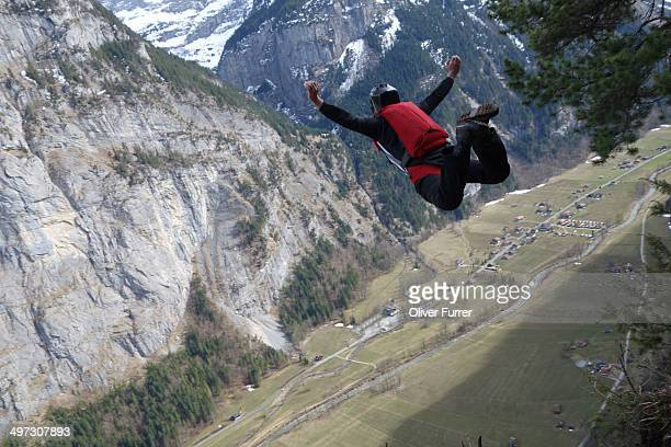 Base jumper is falling down into the valley