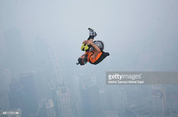 A base jumper is shrouded in haze as he leaps from the 300metre high open deck at Malaysia's Kuala Lumpur Tower during the International Tower Jump...